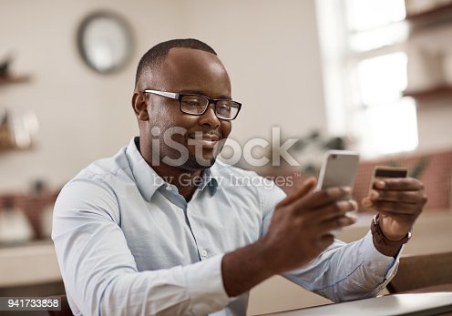 Cropped shot of a handsome young businessman sending a text message while working at home