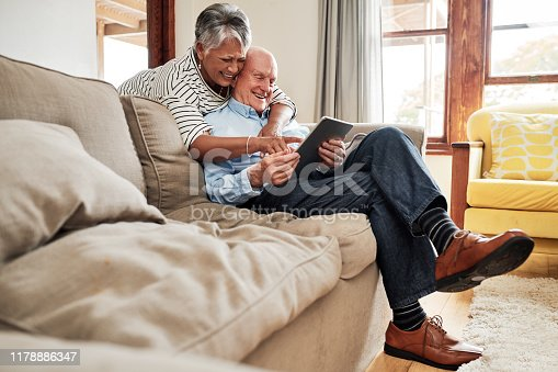 Shot of a senior couple using a digital tablet together on the sofa at home