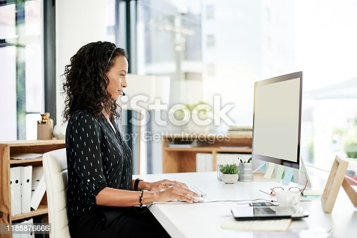 Shot of a young woman using a headset in a modern office