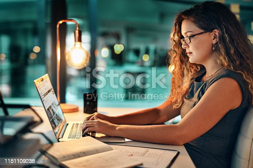 Shot of a businesswoman using her laptop while working late at the office