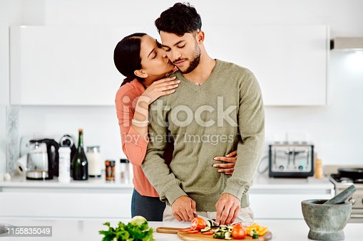 Shot of a woman embracing her boyfriend while he chops vegetables