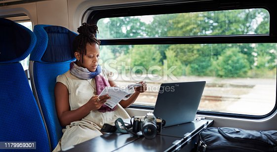Cropped shot of an attractive young woman sitting alone in a train and reading a book during a trip