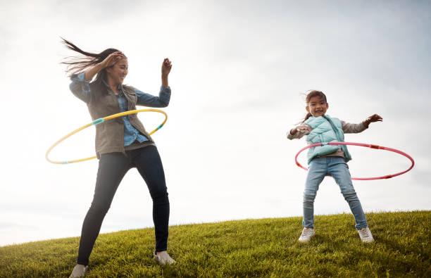 there's nothing like some hula fun - mãe criança brincar relva efeito de refração de luz imagens e fotografias de stock