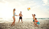 Shot of a family playing catch with a beach ball while enjoying a day at the beach