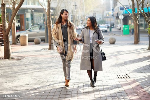 Full length shot of two affectionate young friends having a discussion while walking in the city