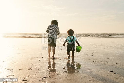 Rearview shot of two adorable young sisters playing together at the beach during sunset