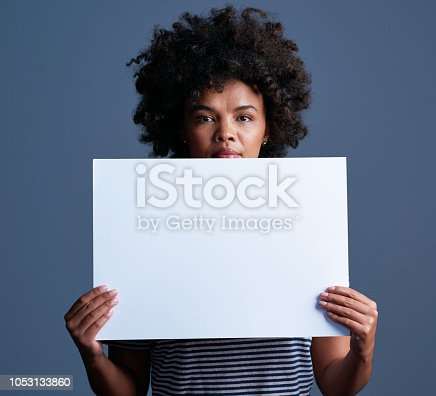 Studio shot of an attractive young woman holding a blank placard against a blue background