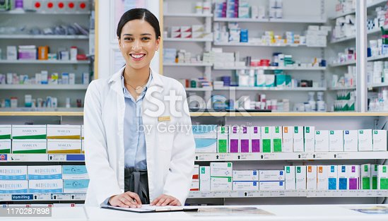 Portrait of a young pharmacist writing notes while working in a chemist