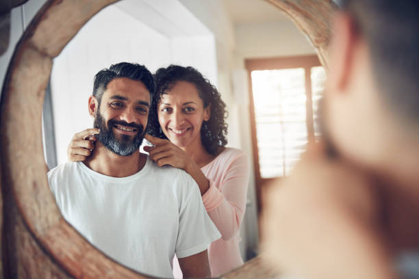 There's the smile I fell in love with Shot of a mature man looking at his reflection in the mirror with his wife encouraging him to smile encouragement stock pictures, royalty-free photos & images