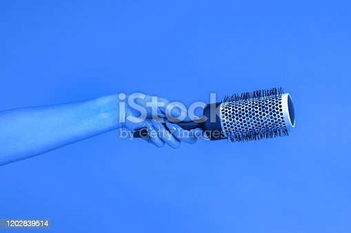 istock Thermal hairbrush in the female hand  on blue background. toned on trendy Classic Blue Color 1202839514