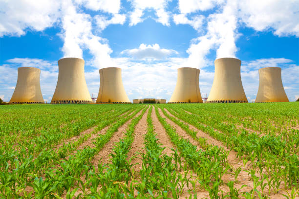 Thermal power plant with corn field. Blue cloudy sky. stock photo
