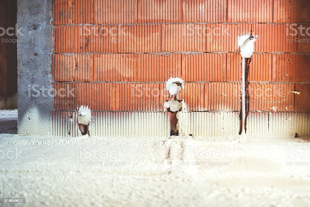 thermo insulation with spray foam, brick walls and electricity lines stock photo