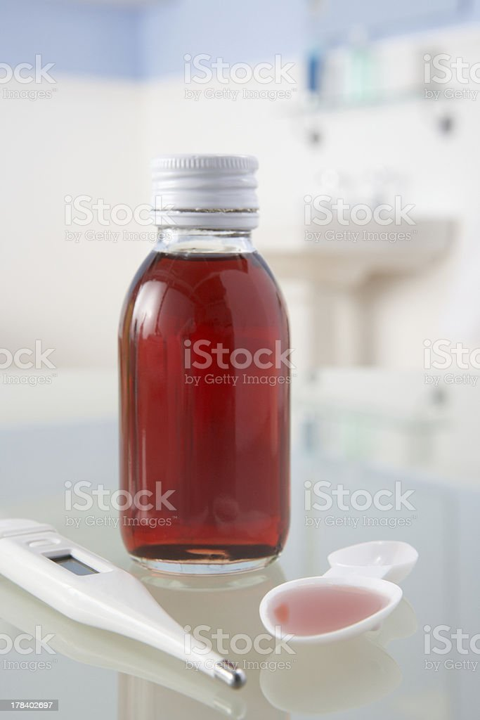 Thermometer and medicine on bathroom shelf stock photo