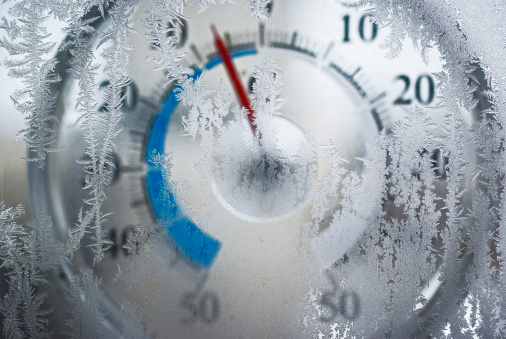 Thermometer for icy window shows the temperature of - 6 degrees Celsius. Red arrow on a blue field. The image is slightly blurry. Frost on the window in focus.