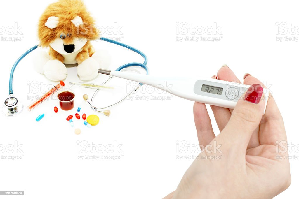 Thermometer in hand and soft toy with a stethoscope stock photo