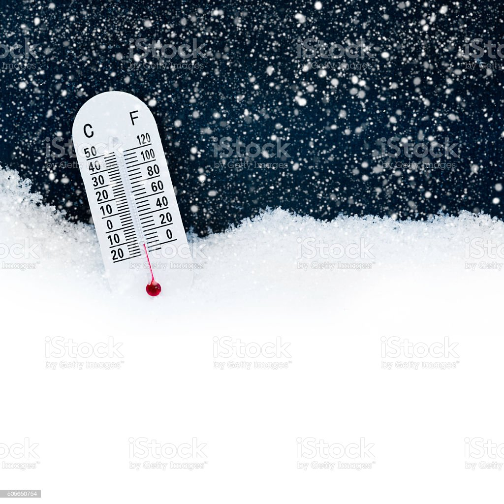 Thermometer in the snow with both celsius and fahrenheit stock photo