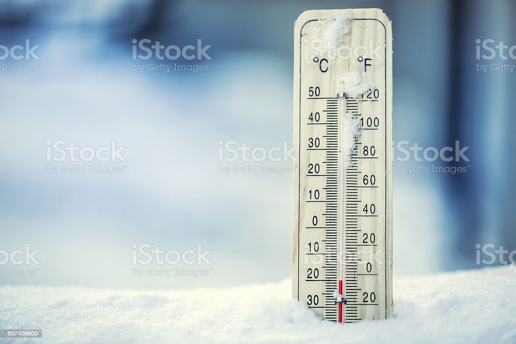 Thermometer on snow shows low temperatures under zero. stock photo
