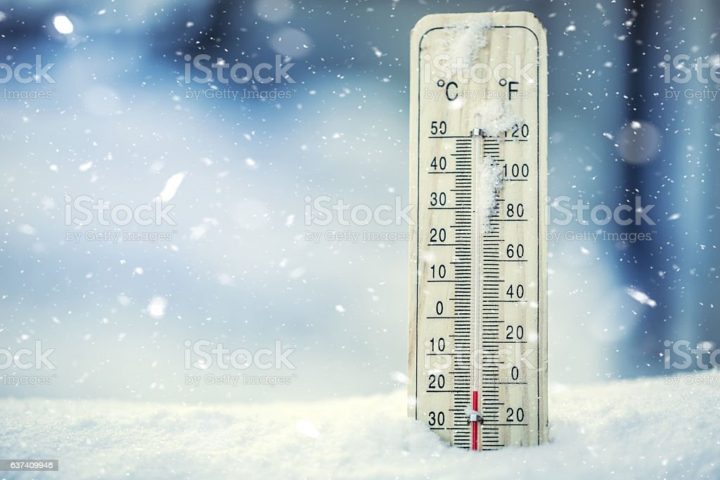Thermometer on snow shows low temperatures under zero.