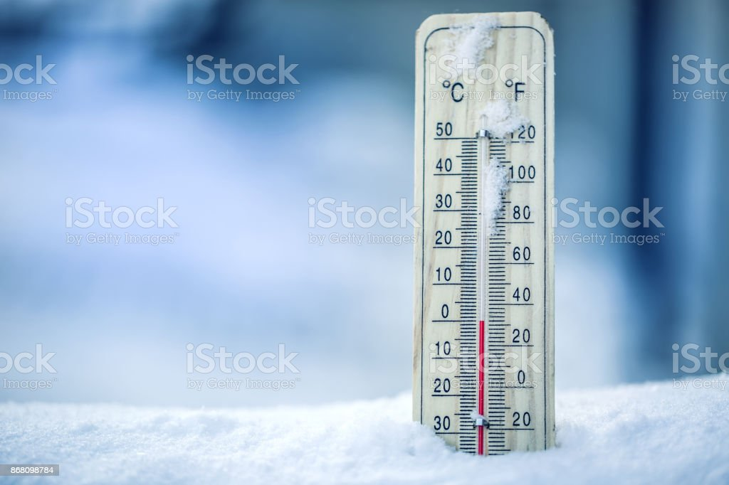Thermometer on snow shows low temperatures - zero. Low temperatures in degrees Celsius and fahrenheit. Cold winter weather - zero celsius thirty two farenheit stock photo
