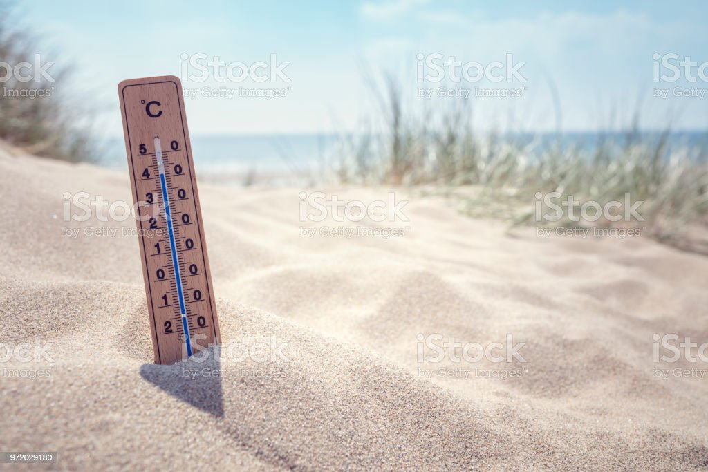 Thermometer on the beach background stock photo