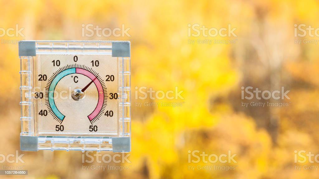 Thermometer On Window And Blurred Yellow Forest Stock Photo