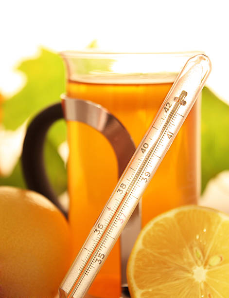Thermometer  with tea and lemon in background  affective stock pictures, royalty-free photos & images