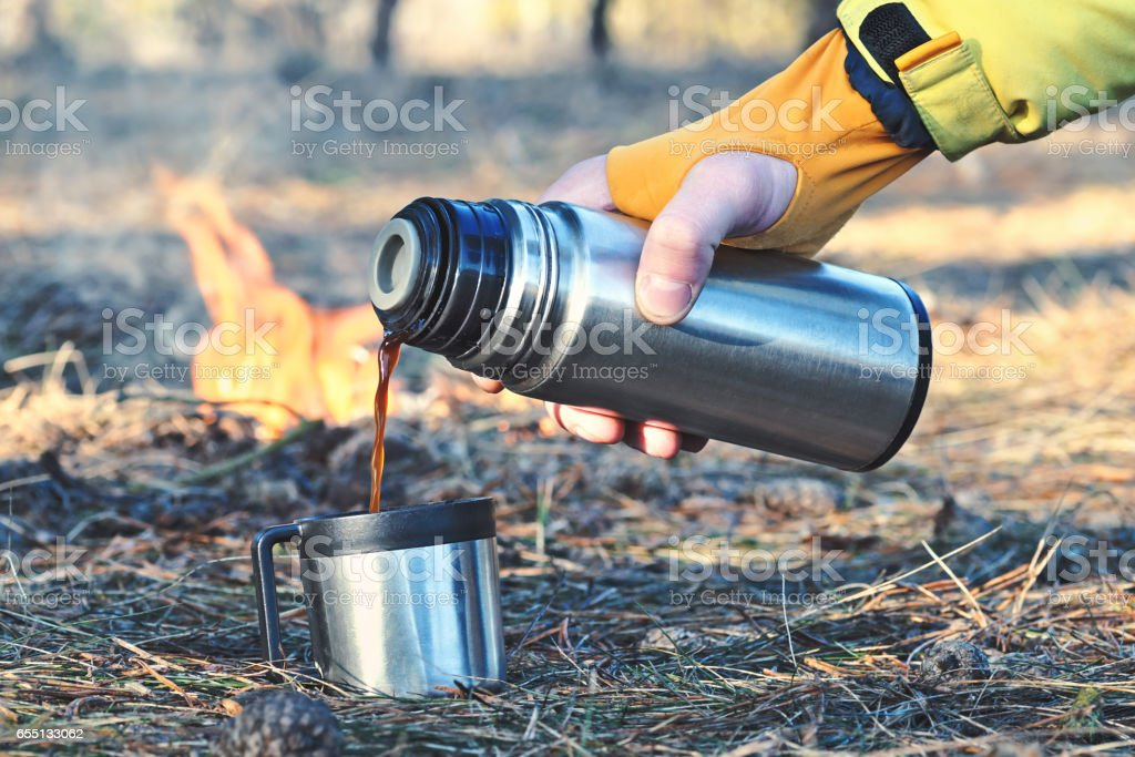 Thermos bottle outdoor near the campfire stock photo