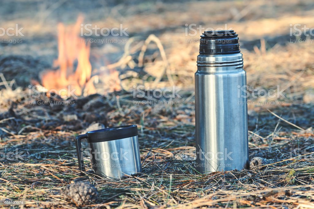 Thermos bottle with coffee or tea outdoor stock photo