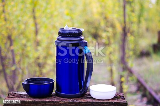 1135476970istockphoto Thermos for drinks. Thermos with two mugs. With a thermos on the nature. Camping with a thermos. Fall. 870943974
