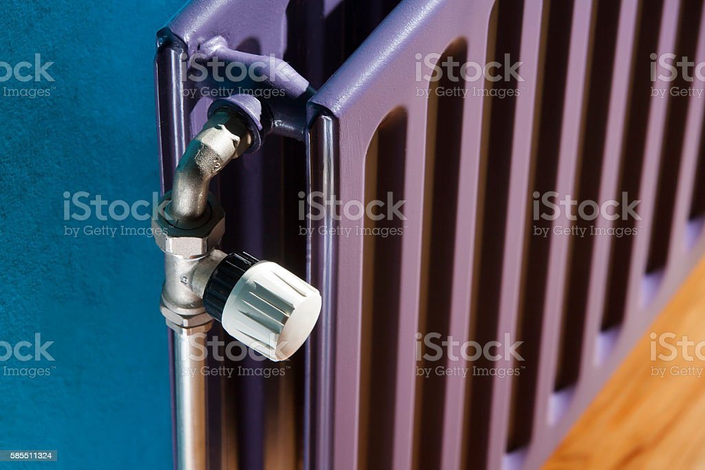 Thermostat on a purple radiator and a blue wall – Foto