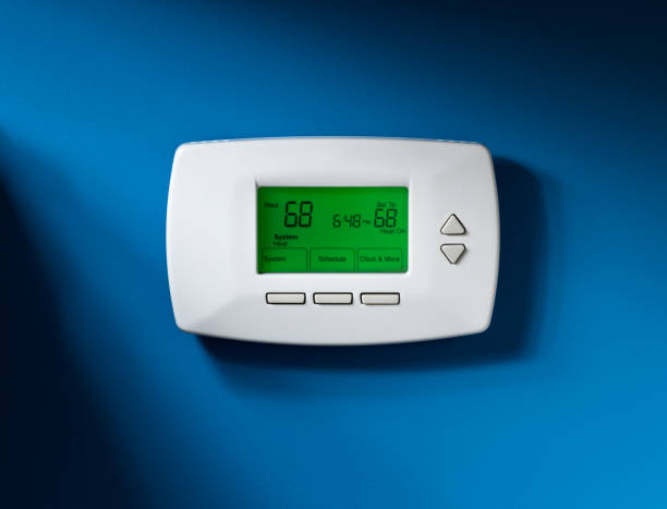 Thermostat, Programmable, Isolated on blue Programmable thermostat set to 68 degrees.  Isolated on blue background with dramatic lighting. burwellphotography stock pictures, royalty-free photos & images