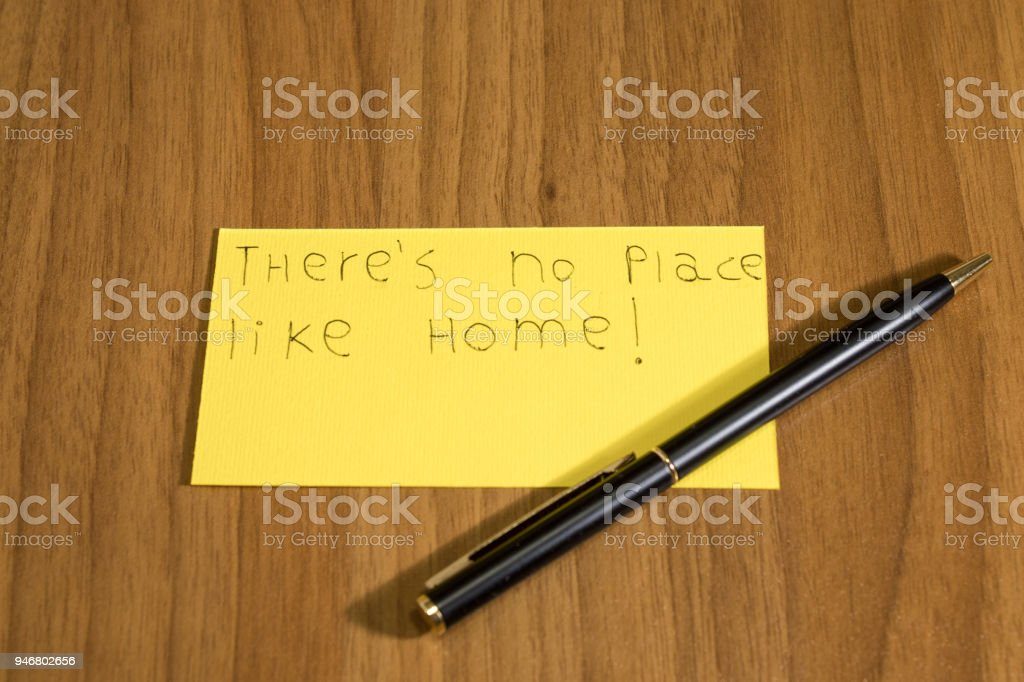 Ther's no place like home handwrite on a yellow paper with a pen composition stock photo