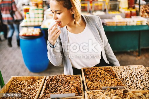 Beautiful blonde woman tasting almonds  at food market.