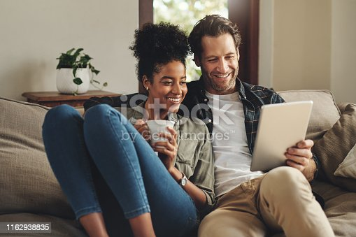 Shot of a happy young couple using a digital tablet together while relaxing on a couch at home
