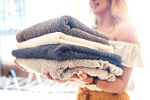 Cropped shot of a young woman holding a clean stack of towels