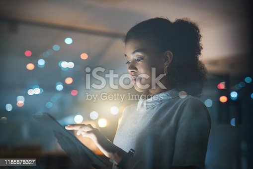 Shot of a young businesswoman using a digital tablet while working late in her office