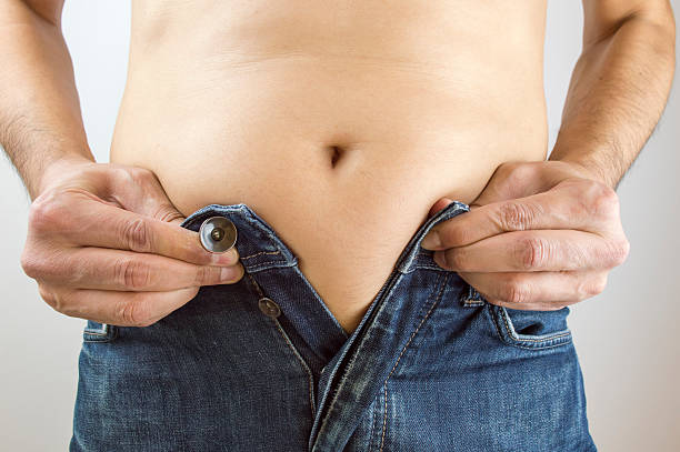 these don t fit anymore Cropped mid section of an obese man trying to close the buttons of his jeans against men in tight jeans stock pictures, royalty-free photos & images