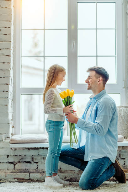 These flowers are for you. Dad gives her daughter a bouquet of tulips. genderblend stock pictures, royalty-free photos & images