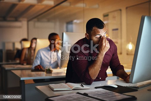 Shot of a young businessman looking stressed out while working late in an office