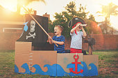 Shot of a cute little boy and his brother playing pirates outside on a boat made of cardboard boxes