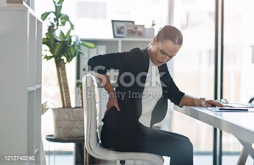 Cropped shot of an attractive young businesswoman suffering from back pain while working inside her office