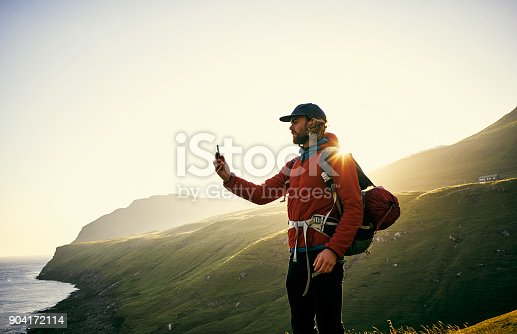 Shot of a young man taking pictures with his cellphone outdoors