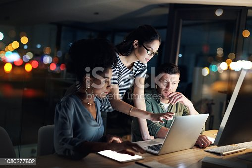 Shot of a group of designers working late on a laptop in an office