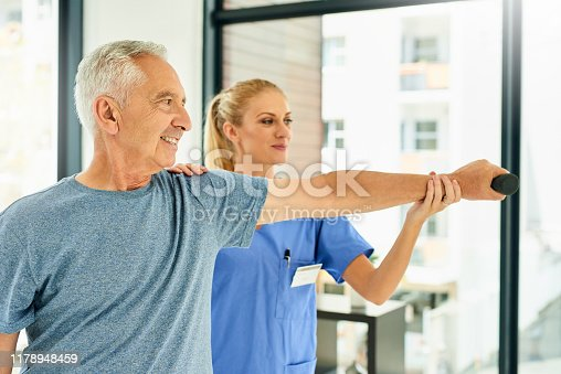 Shot of a physiotherapist assisting a senior patient with strengthening exercises
