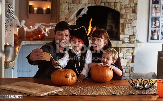 Shot of an adorable young family taking selfies together with a cellphone on halloween at home