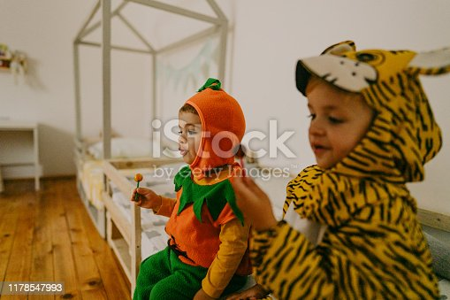 Photo of costumed boys ready for Halloween, eating sweets