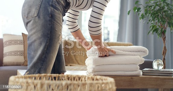 Cropped shot of an unrecognizable woman folding up clean towels at home