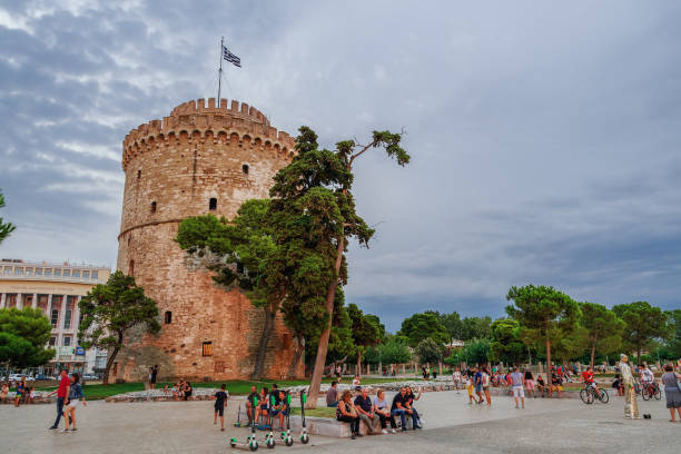 Thessaloniki, Greece - August 15 2019: Golden hour at the city landmark with crowd & Lime-S electric scooters. Evening view of unidentified crowd before White Tower with Greek flag waving on top. stock photo