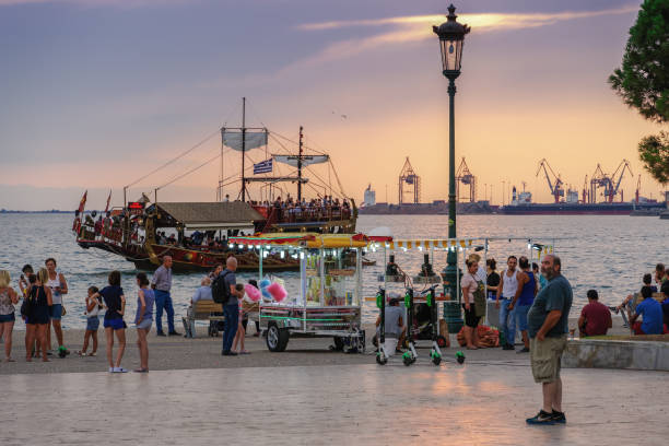 Thessaloniki, Greece - August 15 2019: Golden hour at waterfront with crowd. Thermaikos gulf seafront evening with street vendors & trailer selling cotton candy or popcorn before White Tower landmark. stock photo