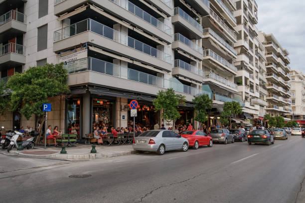 Thessaloniki, Greece - August 15 2019: People enjoy coffee at city center cafe bars. Unidentified crowd drinking frape or other beverage at outdoors seating bars in Nikis Avenue before the waterfront. stock photo